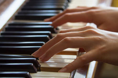 Close view of girls hands on piano photo