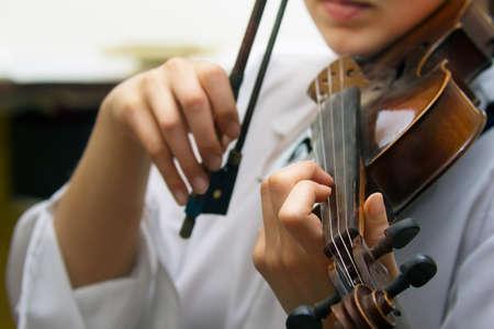 Sluiten oog van meisjes hand op violen snaren Stockfoto
