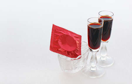 red condom: Close view of red condom in a small vase and two glasses with a dark drink on white background