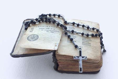 bible ouverte: Antique livre de prières et un chapelet noir sur elle dans un fond blanc Banque d'images