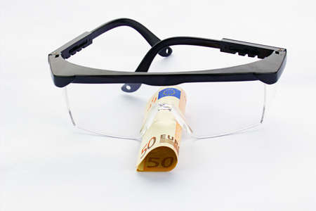protecting spectacles: Protective goggles and fifty euro banknote in a white background