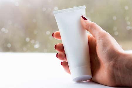 Vrouw hand met witte crème buis in een heldere achtergrond Stockfoto