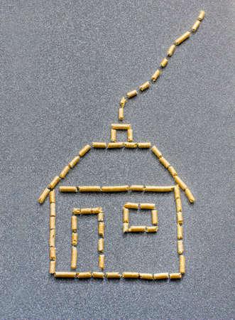 Gestileerde huis gemaakt van hout pellets in een grijze achtergrond