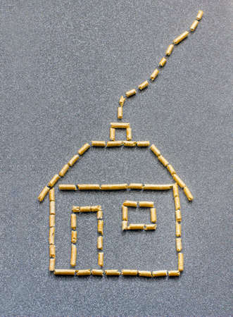 Stylized house made of wood pellets in a grey background Stock Photo