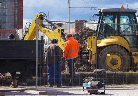 Werknemers en graafmachine op een thermische ondergronds netwerk reparatie
