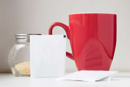 sachets: Close view of blank tea sachet with teabag red teacup and brown sugar Stock Photo