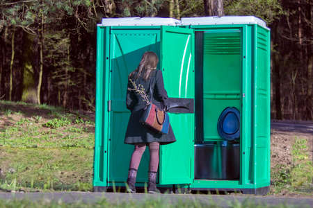 Girl at a portable toilets at an outdoor in the park. The modern plastic portable toilet has been manufactured since the 1960s. Фото со стока