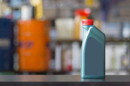 greasing: Recipiente de aceite del motor con la etiqueta en blanco en un fondo borroso colorido Foto de archivo