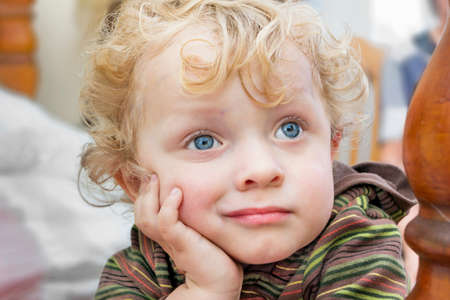 Pensive little boy  with golden curly hair Stock Photo