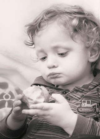 fondo blanco y negro: Retrato de muchacho rubio lindo con manzana en blanco y negro