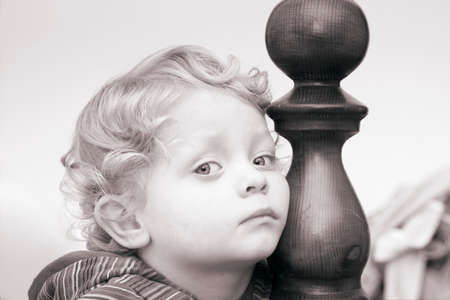 faraway: Pensive little boy  with  curly hair in black white Stock Photo