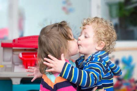 Little curly blond boy kiss a brunette  little girl