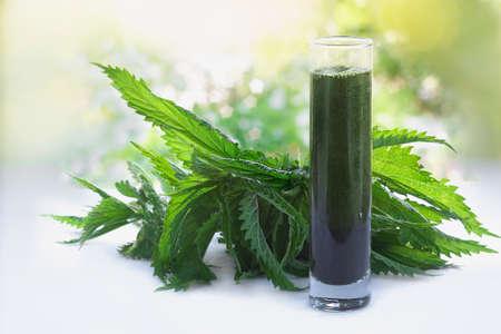 Groene rauwe brandnetels en een smoothie gemaakt van brandnetels sap in een glas Stockfoto