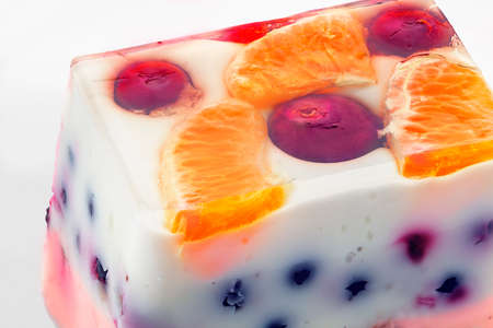 Close view of a piece of a colorful jelly cake with fruits photo