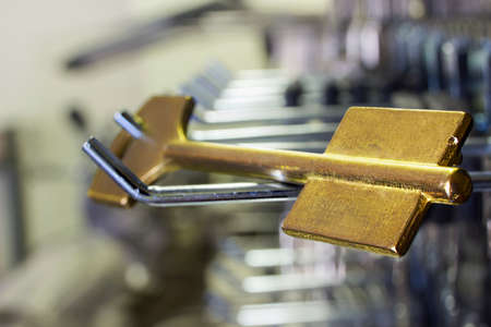 Blank golden key for cutting in a workshop Imagens