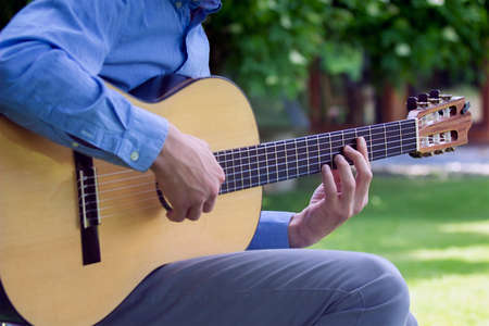 Young male playing a classic guitar outside in summer