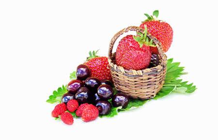 small basket: Wild strawberries cherries and strawberries in a small basket on a white background Stock Photo