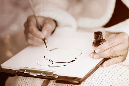 cruet: Females hands drawing a caricature with paintbrush and black ink on a white paper