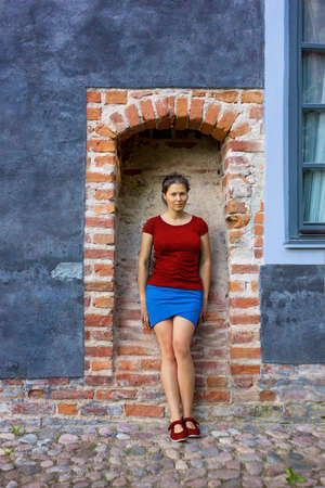 Young woman in a brick arc of castle