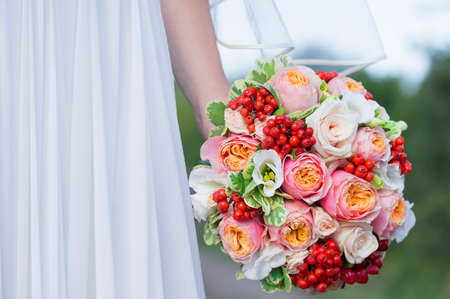 Sluit het oog op mooie kleurrijke bruiloft boeket in een hand van een bruid Stockfoto