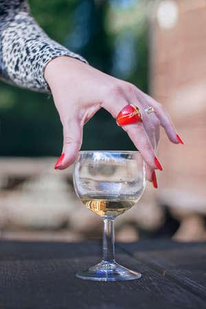 unas largas: Mano de la hembra con largas u�as de color rojo con un vaso de vino en una mesa de madera Foto de archivo