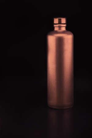 bronze bowl: Bronze colored ceramic bottle in a dark background