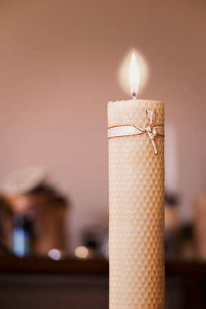 beeswax candle: Close view of a flame of a beeswax candle in a warm background