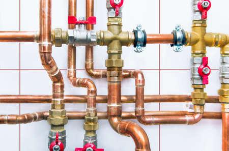 bomba de agua: tubos de cobre del sistema de calefacción con válvulas de bola en una pared blanca