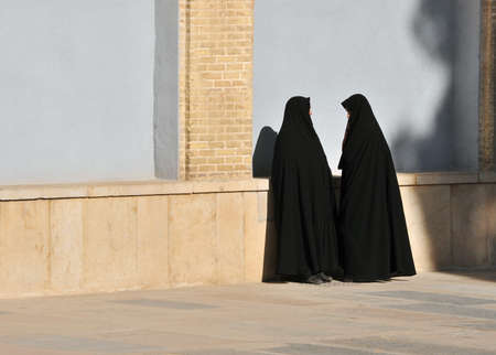 middle eastern clothes: Two muslims woman talk near yellow brick wall Stock Photo