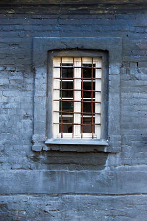 transom: Barred window on an old brick building in blue Stock Photo