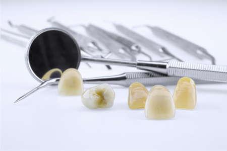 odontologo: Prótesis de cerámica de metal con herramientas de dentista en un fondo blanco Foto de archivo