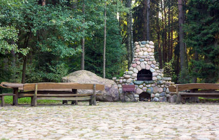 stone fireplace: Stone fireplace and wooden benches in a rural homestead