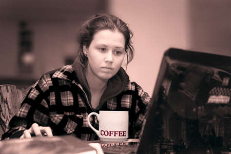 warmly: Warmly dressed young woman using laptop and big cup of coffee