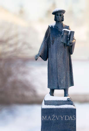 Snow covered the first Lithuanian books author Martynas Mazvydas sculpture in Birstonas resort in Lithuania. Stock Photo