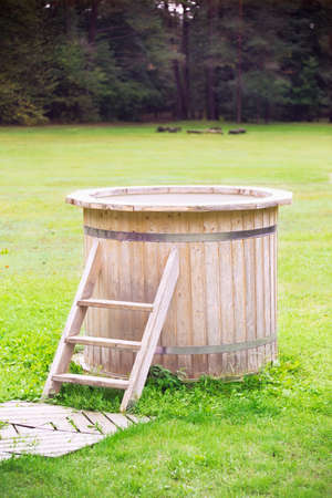 tun: Wooden bathtub with stairs on a grass in a yard Stock Photo