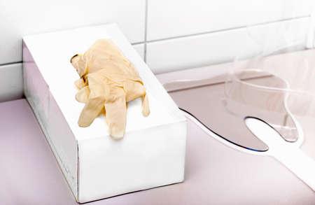 odontologa: cuadro blanco con guantes de látex del dentista y espejo de la forma del diente sobre la mesa en la clínica de odontología