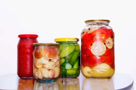 marinated gherkins: Mushrooms and vegetables in glass jars on a table Stock Photo