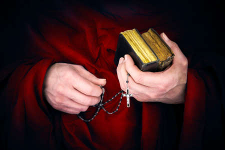 catholic church: Mystery monk with a cape holding bibles and a black rosary in his hands Stock Photo
