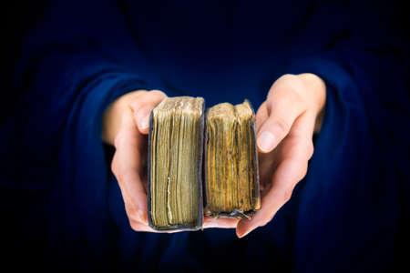 sotana: Manos de la mujer que dan dos libros antiguos en un fondo tonos azul oscuro Foto de archivo