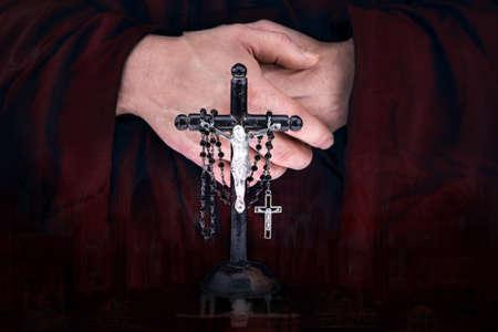 sotana: Cerrar la vista de las manos misterio de monje con un cabo, crucifijo y un rosario negro Foto de archivo