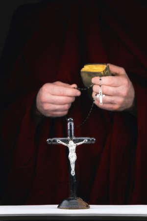 sacerdote: Cerrar la vista de las manos misterio de monje con un cabo, biblia, un rosario y un crucifijo negro