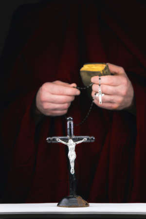cassock: Close view of mystery monks hands with a cape,  bible,  a black rosary and crucifix