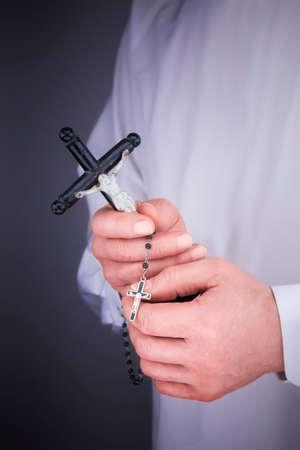 sacerdote: Cerrar la vista de las manos del hombre con una capa blanca, crucifijo y un rosario negro