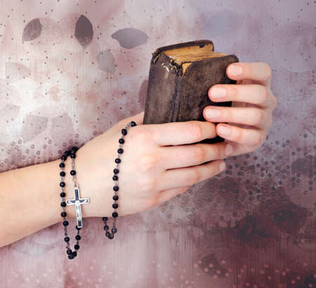 womans clothing: Young womans hands with a rosary, bible and a white clothing in a background
