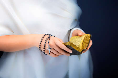 woman's clothing: Young womans hands with a rosary, bible and a white clothing in a background