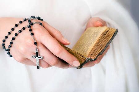 COMUNION: manos de la mujer joven con un rosario, biblia y la ropa blanca en un fondo