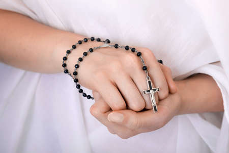 womans clothing: Young womans hands with a rosary and a white clothing in a background Stock Photo