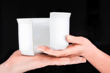 broken unity: Caucasian couple   holding a broken mug  in a black background