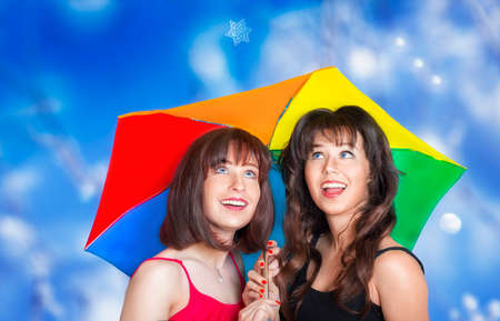 hilarity: Two smiling girls with colorful umbrella looking at the snowflake falling Stock Photo