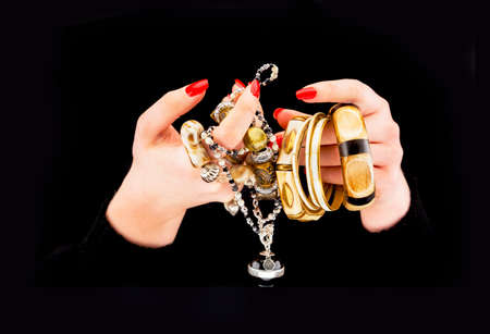 womans hands: Womans hands with various bracelets in a black background